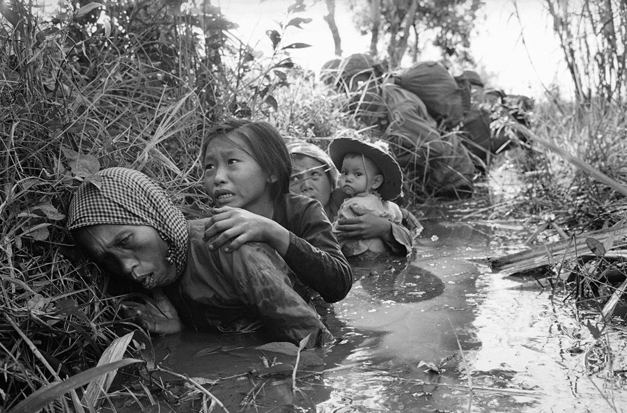 1 Women and children crouch in a muddy canal as they take cover from intense Viet Cong fire at Bao Trai, about 20 miles west of Saigon, Vietnam, on January 1, 1966 - Horst Faas.jpg